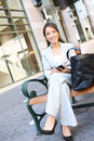 Asian Business Woman on Bench Outside Office Stock Photos