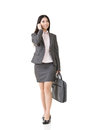 Asian business woman talking on the cell phone walking and mobile in one hand and handbag in another full length isolated white Stock Images