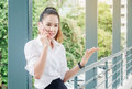 Asian business woman wearing white shirt talking smartphone for Royalty Free Stock Photo