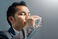 Asian Businessman in grey suit drinking water. Healthy. Copy spa Royalty Free Stock Photo