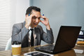 Asian Businessman in grey suit thinking and looking to his laptop. Man has stressed and headache from migraine. Royalty Free Stock Photo