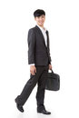 Asian businessman hold briefcase and walk full length portrait isolated on white background Royalty Free Stock Images