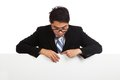 Asian businessman look down behind blank banner Royalty Free Stock Photo