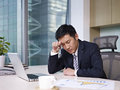 Asian businessman sitting in office looking tired Royalty Free Stock Photos