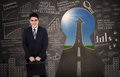 Asian businessman standing in front of keyhole and arrow sign outside Stock Photo