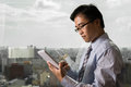 Asian businessman using tablet in the office with glass window over city Royalty Free Stock Photos