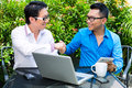 Asian businessmen working outdoor businesspeople they sitting with laptop in a cafe and brainstorming Royalty Free Stock Images