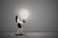 Asian businesswoman is carrying bright light bulb on grey background Stock Photography