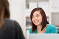 Asian businesswoman chatting to a colleague smiling female as she sits at her desk in the office Royalty Free Stock Image