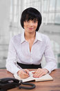 Asian businesswoman sitting at table in office and writing book Royalty Free Stock Photos