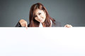 Asian businesswoman stand behind a blank billboard , point down Royalty Free Stock Photo