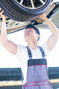Asian car mechanic changing auto tire Royalty Free Stock Photo