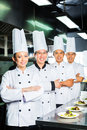 Asian chef in restaurant kitchen cooking indonesian and chinese chefs along with other cooks or hotel commercial finishing dish or Royalty Free Stock Images