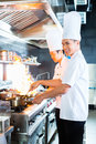Asian chefs cooking in restaurant side view of together Stock Images