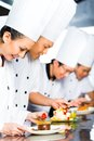 Asian chefs in restaurant kitchen cooking indonesian chef along with other cooks or hotel finishing dish or plate for dessert Stock Photo