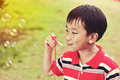 Asian child blowing soap bubbles in summer park, nature backgrou Royalty Free Stock Photo