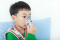 Asian child holds a mask vapor inhaler for treatment of asthma. Royalty Free Stock Photo