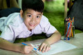 Asian child in student uniform painting on a white paper Royalty Free Stock Photo