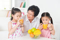 Asian children drinking orange juice family happy grandparent and grandchildren enjoying cup of fresh squeeze fruit at home Stock Photos