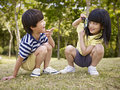 Asian children playing with magnifier outdoors Royalty Free Stock Photo
