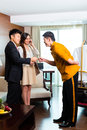 Asian chinese bell boy or porter receiving tip baggage bellboy page for delivering the suitcase of guests to the hotel room suite Stock Photography
