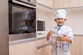 Asian chinese boy in white chef uniform baking cookies at home Stock Photo