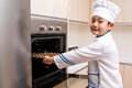 Asian chinese boy in white chef uniform baking cookies at home Stock Photography