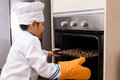 Asian chinese boy in white chef uniform baking cookies at home Royalty Free Stock Photos