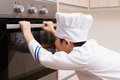 Asian chinese boy in white chef uniform baking cookies at home Royalty Free Stock Image