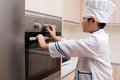 Asian chinese boy in white chef uniform baking cookies at home Royalty Free Stock Photography