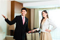 Asian chinese hotel manager presenting suite or director or supervisor arriving vip guests the room or Stock Images