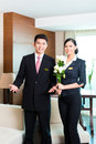 Asian chinese hotel manager welcoming vip guests or director and supervisor welcome arriving with roses on arrival in luxury or Royalty Free Stock Photo