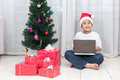 Asian Chinese little boy with laptop beside Christmas presents Royalty Free Stock Photo
