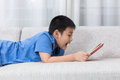 Asian Chinese little boy reading book on the sofa Royalty Free Stock Photo