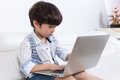 Asian Chinese little boy sitting on the couch with laptop Royalty Free Stock Photo