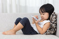 Asian Chinese little girl lying on the sofa with phone Royalty Free Stock Photo