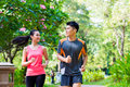 Asian Chinese man and woman jogging in park Royalty Free Stock Photo