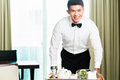 Asian chinese room waiter serving guests food in hotel service or steward a grand or luxury Royalty Free Stock Photo