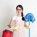 Asian chinese woman housekeeping portrait of holding bucket and mop on plain background Stock Photography