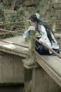 Asian Chinese woman in traditional Blue and white Hanfu dress, play in a famous garden Climb on the bent bridge Royalty Free Stock Photo