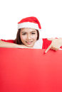 Asian christmas girl with santa claus clothes point down to blan blank sign isolated on white background Stock Photography