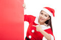 Asian Christmas girl with Santa Claus clothes point to blank sig Royalty Free Stock Photo