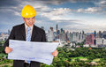 Asian civil engineer in hardhats taking a look at the blueprint in urban environment Royalty Free Stock Photography