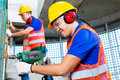 Asian construction workers drilling in building walls indonesian site with a machine or drill bubble level ear protection gloves Royalty Free Stock Photos