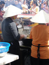 Asian cooks serving food at concessions Royalty Free Stock Photo