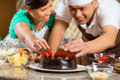 Asian couple baking chocolate cake in kitchen homemade with cherries their for dessert Stock Image