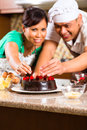 Asian couple baking chocolate cake in kitchen homemade with cherries their for dessert Royalty Free Stock Image