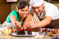 Asian couple baking chocolate cake in kitchen homemade with cherries their for dessert Royalty Free Stock Photos