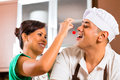 Asian couple baking chocolate cake in kitchen teasing each other while Royalty Free Stock Photography