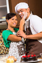Asian couple baking chocolate cake in kitchen teasing each other while Stock Photography